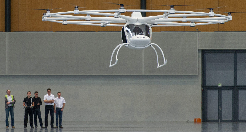 epa03958351 An unmanned electric powered vertical take-off aircraft called 'Volocopter' takes off during its presentation in the dm-Arena in Karlsruhe, Germany, 20 November 2013. The helicopter-like vehicle is propelled by electric motors and is either remotely controlled with a joystick or flying by autopilot. In a later stage of the development it is planned to have the aircraft capable to carry two people, their contructors Thomas Senkel, Stephan Wolf and Alexander Zosel said.  EPA/UWE ANSPACH