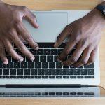 man typing on keyboard password